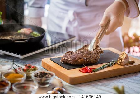 Tongs holding cooked meat. Roasted garlic and green herb. Ribeye steak with chili peppers. For lovers of beef.
