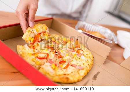 People taking out a slice of pizza in a box