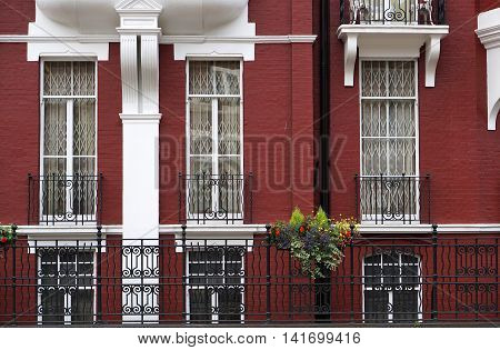 Side view of windows and railings of a striking red and white upscale town house apartment complex