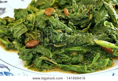 Close up view of the traditional Chinese vegetable side dish of spinach cooked with fermented tofu