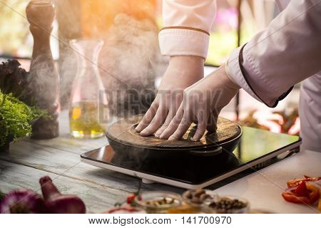 Wooden board covers frying pan. Hands of chef in uniform. It's a secret dish. Surprise for gourmets.