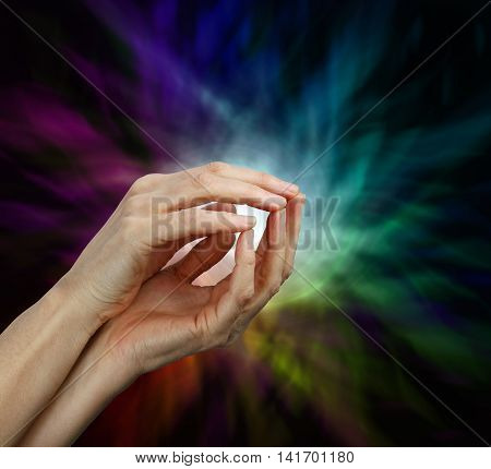 Psychic Protection - a pair of female hands with finger tips touching shaped into a gentle open cage and a multicolored radiating energy formation against a black background