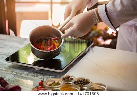 Hand in glove holding saucepan. Slices of colorful vegetables. Spicy peppers for sauce. Secrets of culinary art.