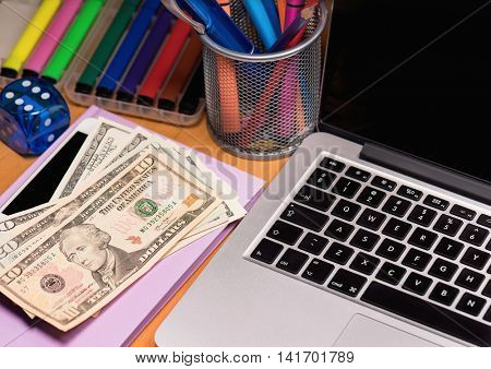 Workplace with money and notebook - US dollar banknotes and laptop computer.