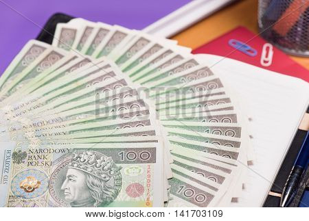 Notepad with Polish money banknotes on table
