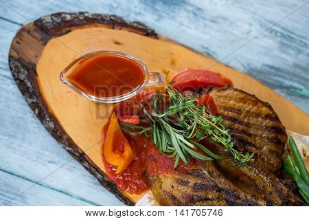 Cooked meat with green herbs. Bowl of red sauce. Grilled pork served in bistro. Traditions of national cuisine.