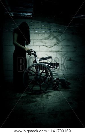 Ghost woman with wheelchair in asylum,Scary background for book cover