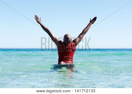 African Man Standing In Sea With His Hands Raised