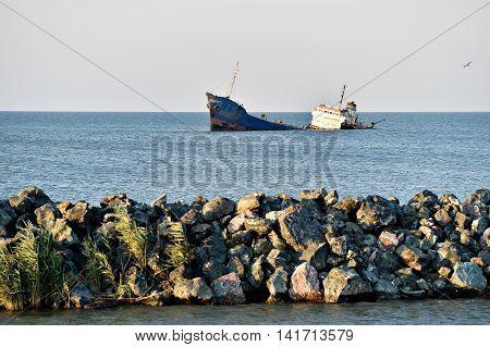 Industrial shipwreck abandoned into sea near the coastline