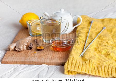 Herbal tea in glass cup with flowers of chamomile, turmeric and honey on a wooden board. Treatment with a cold drink. Treatment of folk remedies in bed. Knitting hobby.