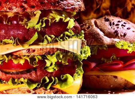 Wooden board double patty hamburger on background of fire. Group of hamburger close up. Hamburger with cheese.