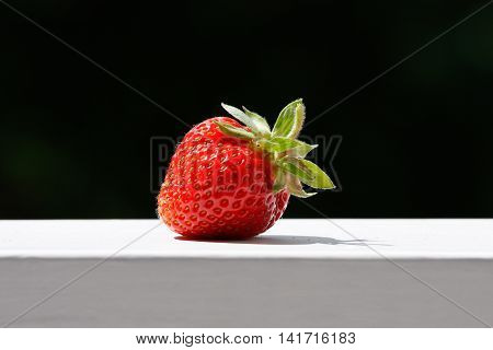 One strawberry on wood railing outdoors summertime.