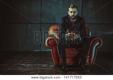 Young handsome businessman with beard in black suit sitting on chair and talking with speaker. Film style retro colors effect.