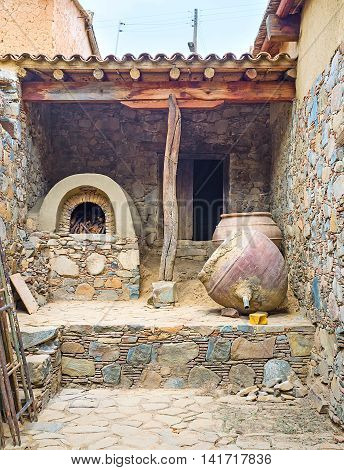 The traditional open air kitchen of abandoned house with the oven of stone and clay and large amphoras Fikardou village Cyprus.
