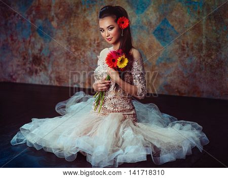 Young asian woman in dress with flowers sitting on floor fashion portrait