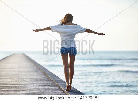 Young beautiful woman teetering on the edge of the pierr