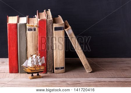 Old vintage books standing in a row on a wooden bookshelf.