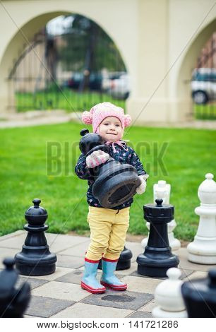 Little Girl Taking A Chessman