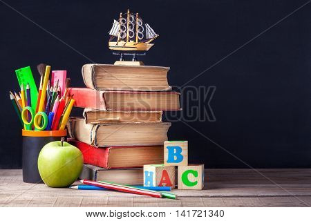 Old textbooks and school supplies are on the rustic wooden table on a background of black chalk board. A glass with colored pencils and dice with the letters.