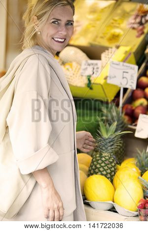 blond woman in front of fruit stand looking at camera