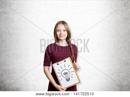 Young woman in red dress with braided light hair is standing at whiteboard background and holding clipboard with light bulb sketch on it. Concept of finding a good idea. Mock up