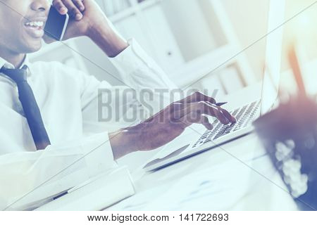 Side view of attractive african american businessperson using notepad and laptop on office desktop while having mobile phone conversation. Bookshelf with documents in the background. Film effect