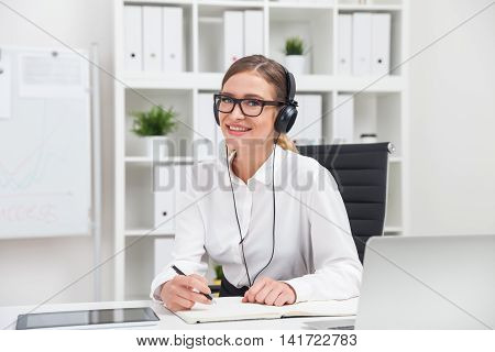 Business lady smiling and listening to music at her workplace during lunch break. Concept of relaxation importance at work.