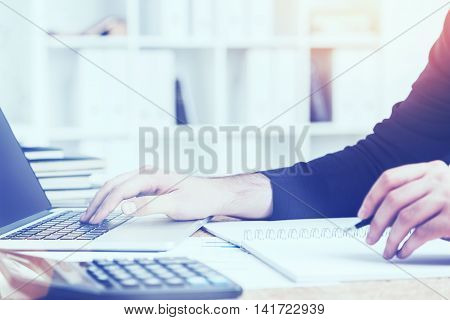 Side view of accountant's hands doing paperwork on cork desktop with calculator and laptop keyboard on office interior background. Film effect