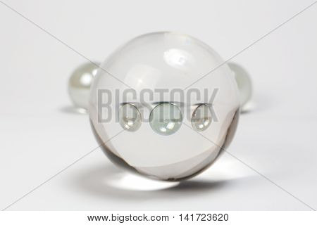 Clear Marbles through Crystal Ball abstract o white background