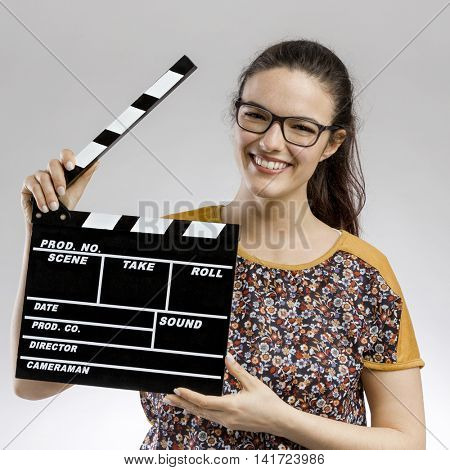 Portrait of a happy woman playing with a clapboard