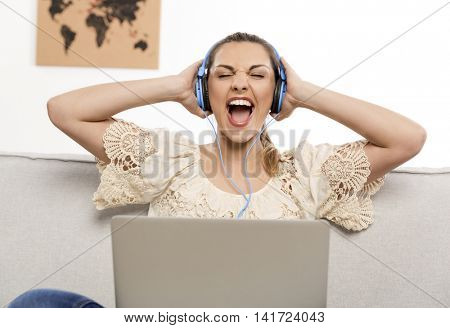Beautiful woman at home working on her laptop and listening music