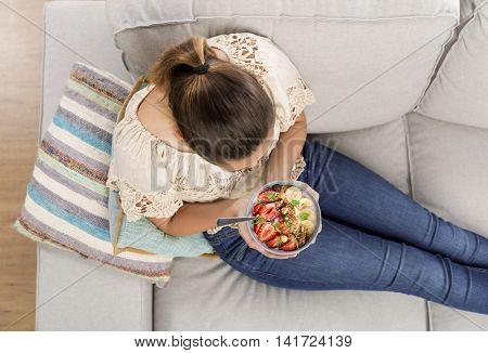 Top viw of a beautiful woman at home eating a healthy bowl