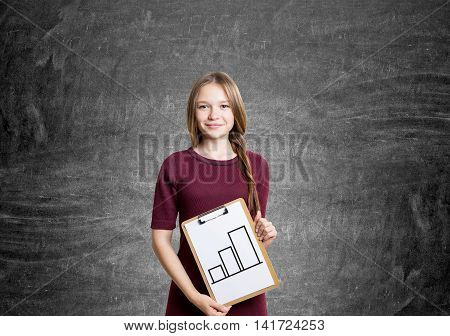 Young woman in red dress with braided hair is standing and holding clipboard with diagram sketch. Background is blackboard. Concept of importance of research and data analysis in business. Mock up