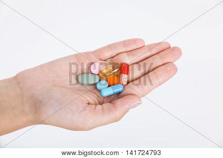 Woman's hand holding heap of pills. Concept of modern medicine