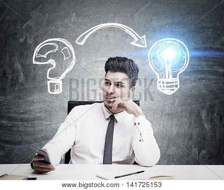 Man in tie and shirt sitting at table against blackboard background and looking for problem solution. Concept of original idea. Toned image
