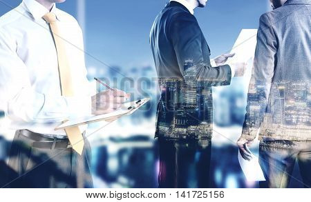 Businesspeople working on illuminated night city background. Teamwork and partnership concept. Double exposure