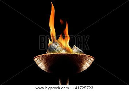 close up shot of money burning in flaming torch.