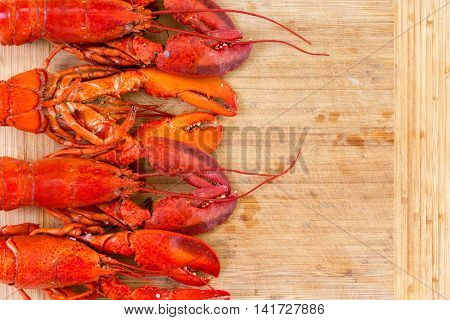 Border Of Four Red Lobsters On A Wooden Board