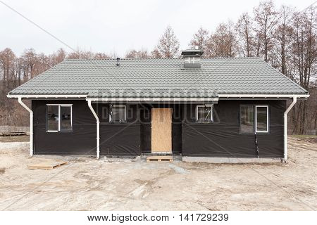 SIP panel house with new gray metal tile roofwhite rain gutter and insulation