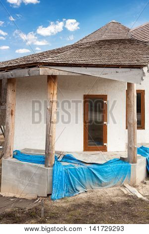 Construction of adobe house with thatched roof and plastic windows