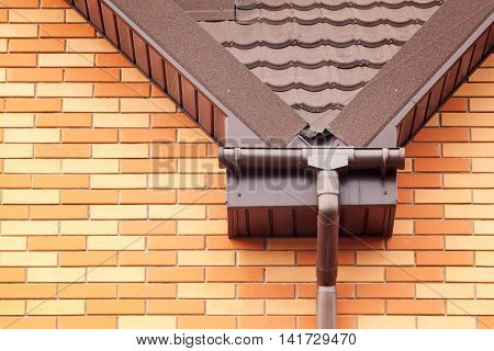 New brown rain gutter with metal tile on a new brick house