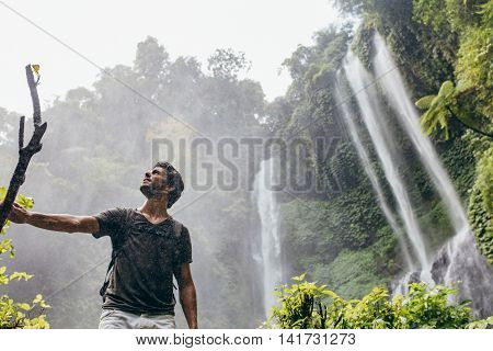 Low angle shot of young man standing near a waterfall in forest and looking away. Male hiker enjoying in the nature with rain.