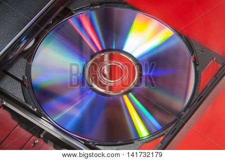 DVD disc in player of a desktop computer with a red background
