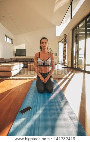 Shot of young woman practicing yoga in living room. Fitness model sitting Vajrasana yoga position on exercise mat at home.