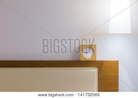 Bed headboard white pillow small clock and over head lamp in simple and minimalist design with room for copy space