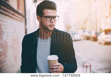Coffee on the go. Handsome young man in smart casual wear walking along the street while holding coffee cup