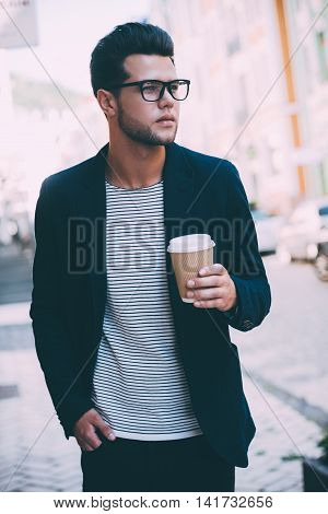 Drinking coffee on the go. Handsome young man in smart casual wear walking along the street while holding coffee cup