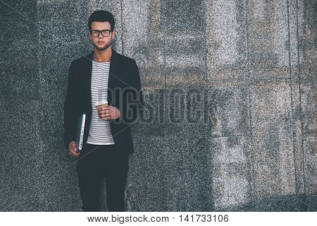 Modern man. Handsome young man in smart casual wear carrying laptop and coffee cup while standing against grey wall and looking at camera