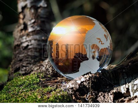 Transparent ball in the green forest. In the field of reflected sunset pipes city. Glass - a material concepts and themes urban ecology emissions environmental protection