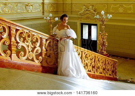 a young lady in a luxurious white dress is going upstairs in the unique theatre